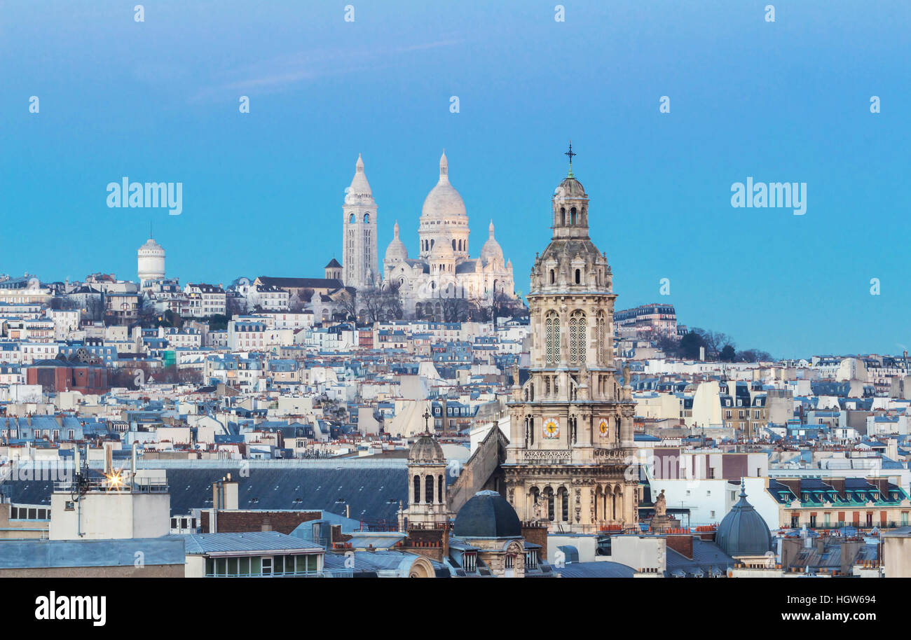 The basilica Sacre Coeur and parisian houses and Saint Trinity church in the foreground, Paris, France - Stock Image