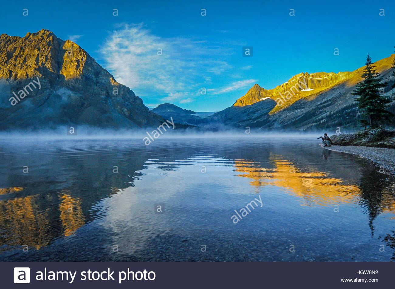 A photographer admires reflections of Crowfoot Mountain and Mount Thompson in Bow Lake. - Stock Image