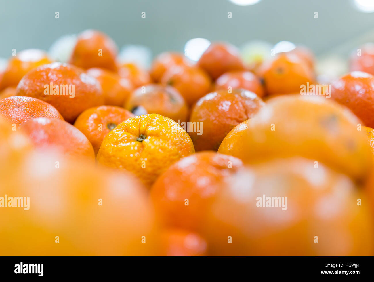 Macro closeup of display of many tangerine oranges in store - Stock Image