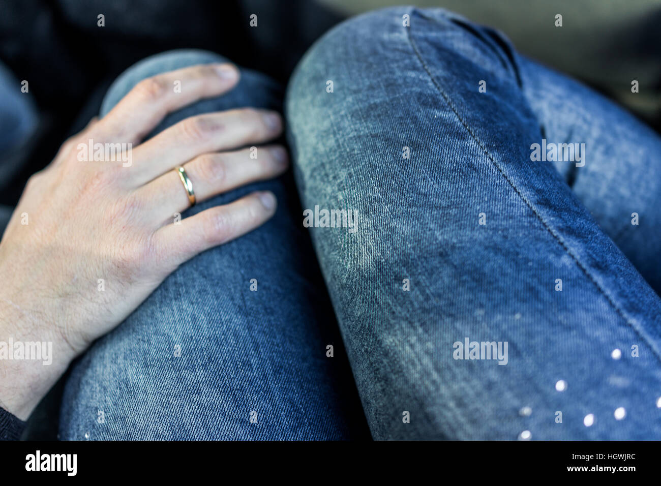Man's hand with wedding ring on woman's legs in jeans in car - Stock Image