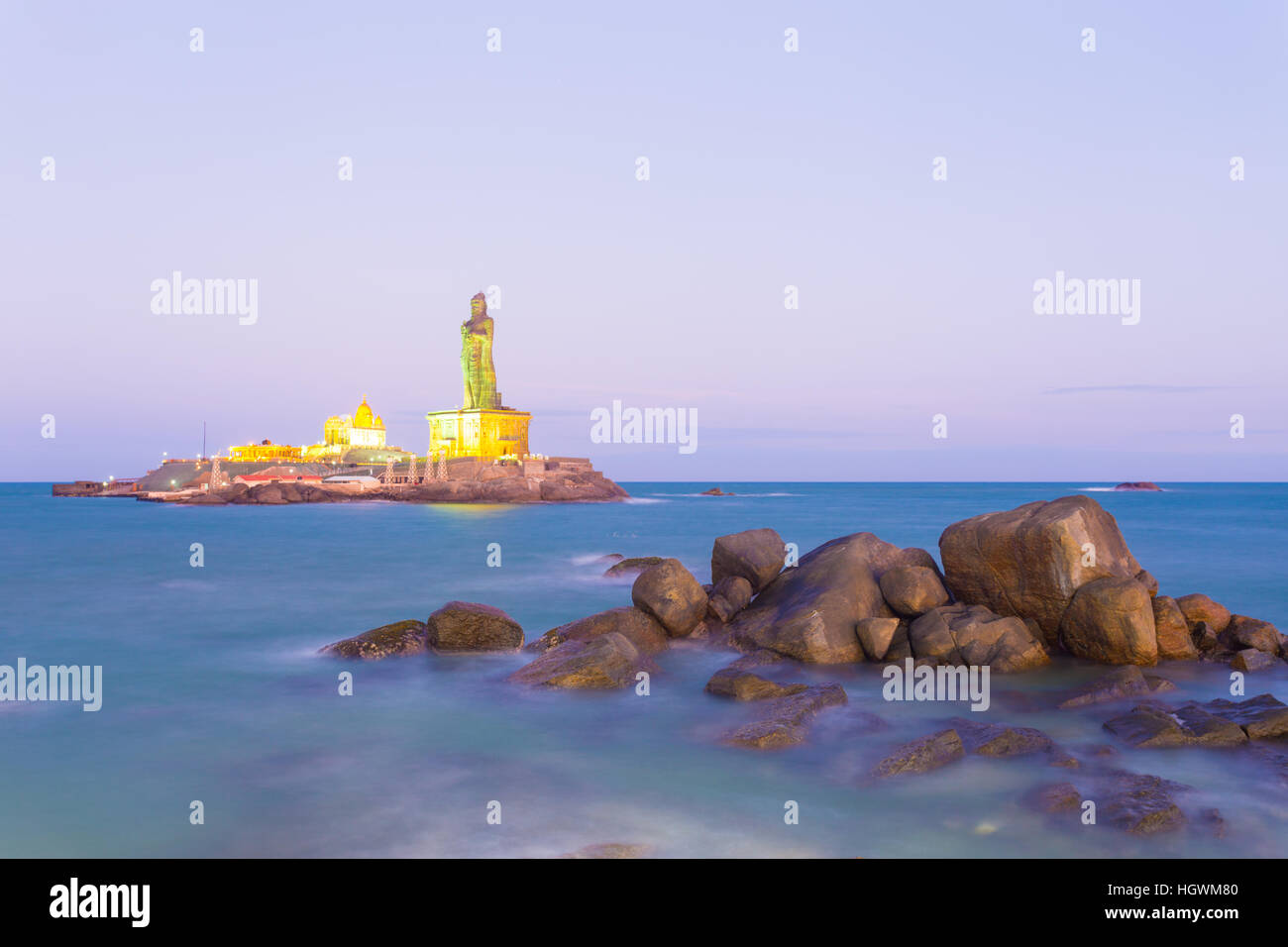 Vivekananda Rock is home to a memorial and neighboring island Thiruvalluvar Statue lighted at dusk blue hour in - Stock Image