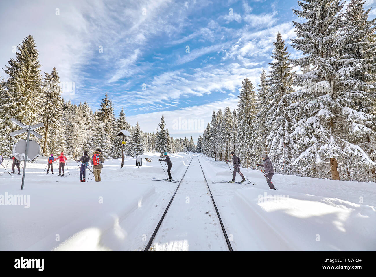 Jakuszyce, Poland - January 07, 2017: Cross-country skiers passing railroad track in forest. - Stock Image