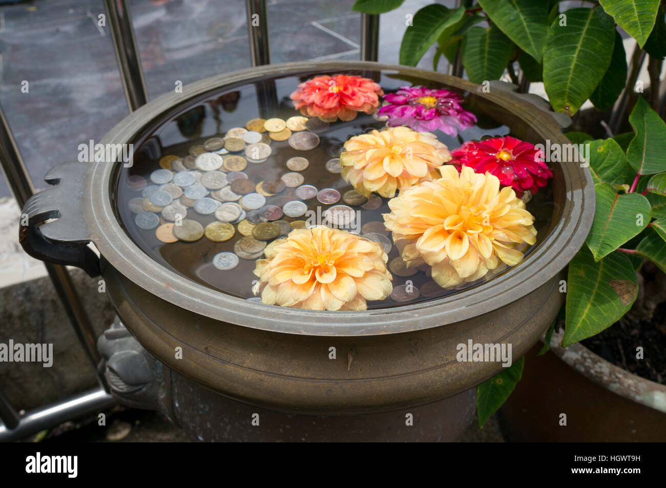 A small floral wishing well with coins on Penang Hill, Malaysia - Stock Image