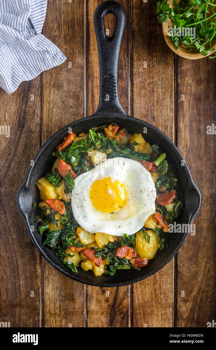 Chorizo and kale hash with a fried egg - Stock Image