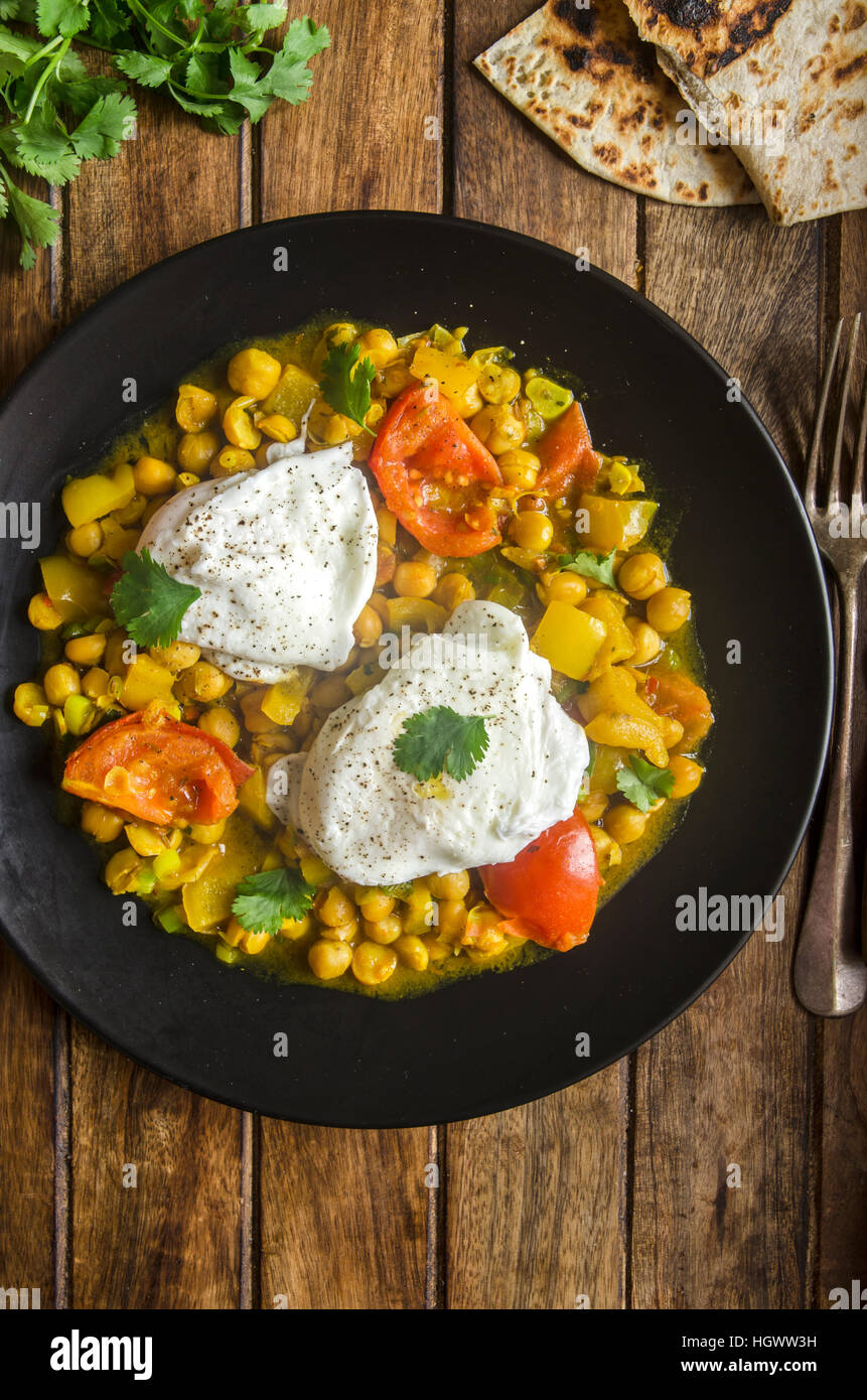 Indian chickpeas with poached eggs and chapatis bread - Stock Image