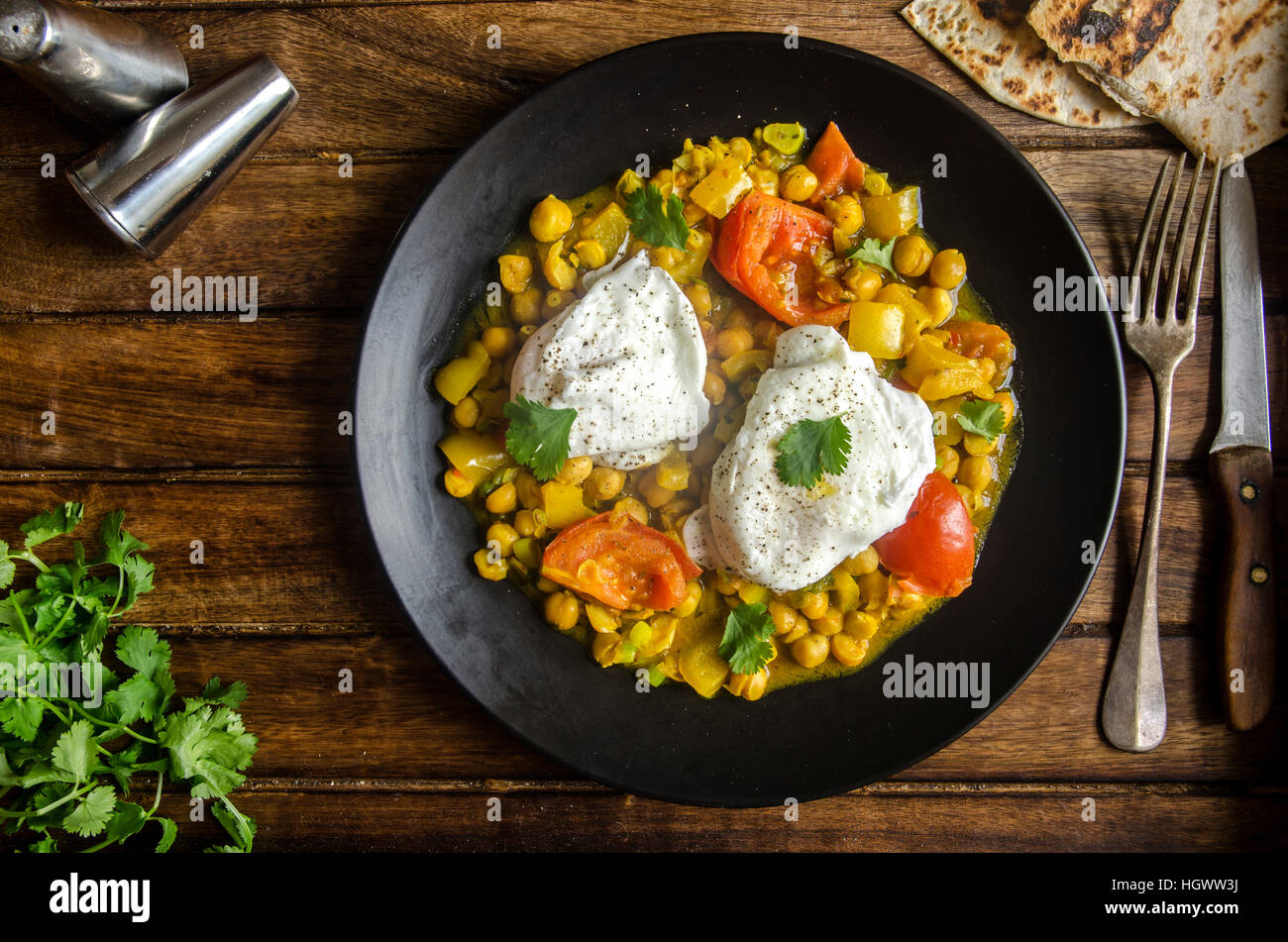 Indian chickpeas with poached eggs and chapatis bread Stock Photo