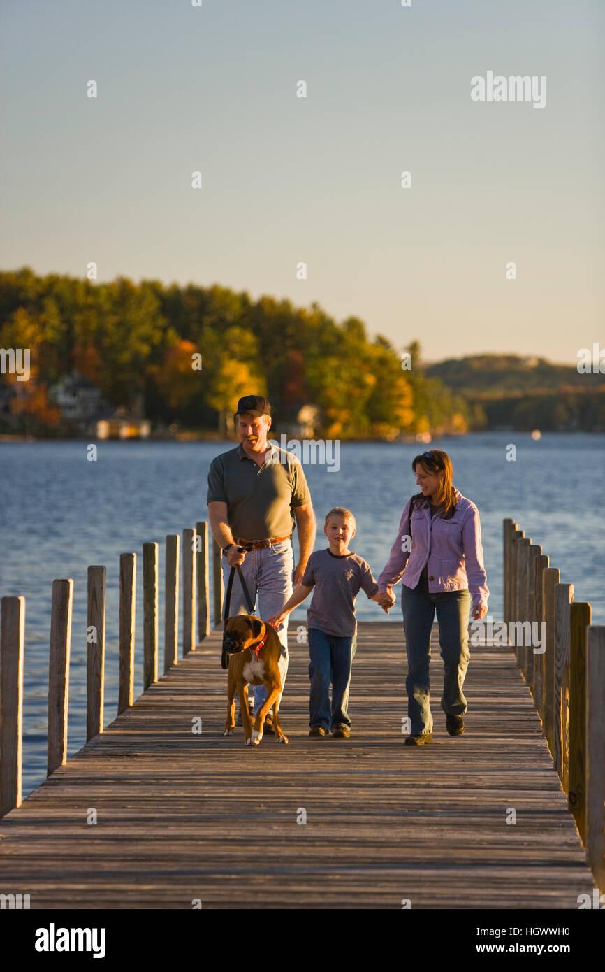 A family walks on the town docks on Lake Winnipesauke in Wolfeboro, New Hampshire. - Stock Image
