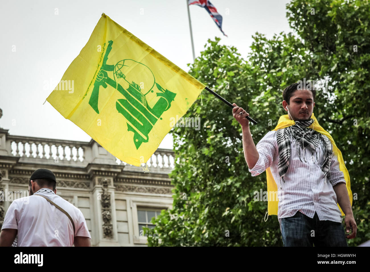 Supports wave flag of Hezbollah. Protest march against the violence used by Israeli soldiers during the Gaza Flotilla - Stock Image