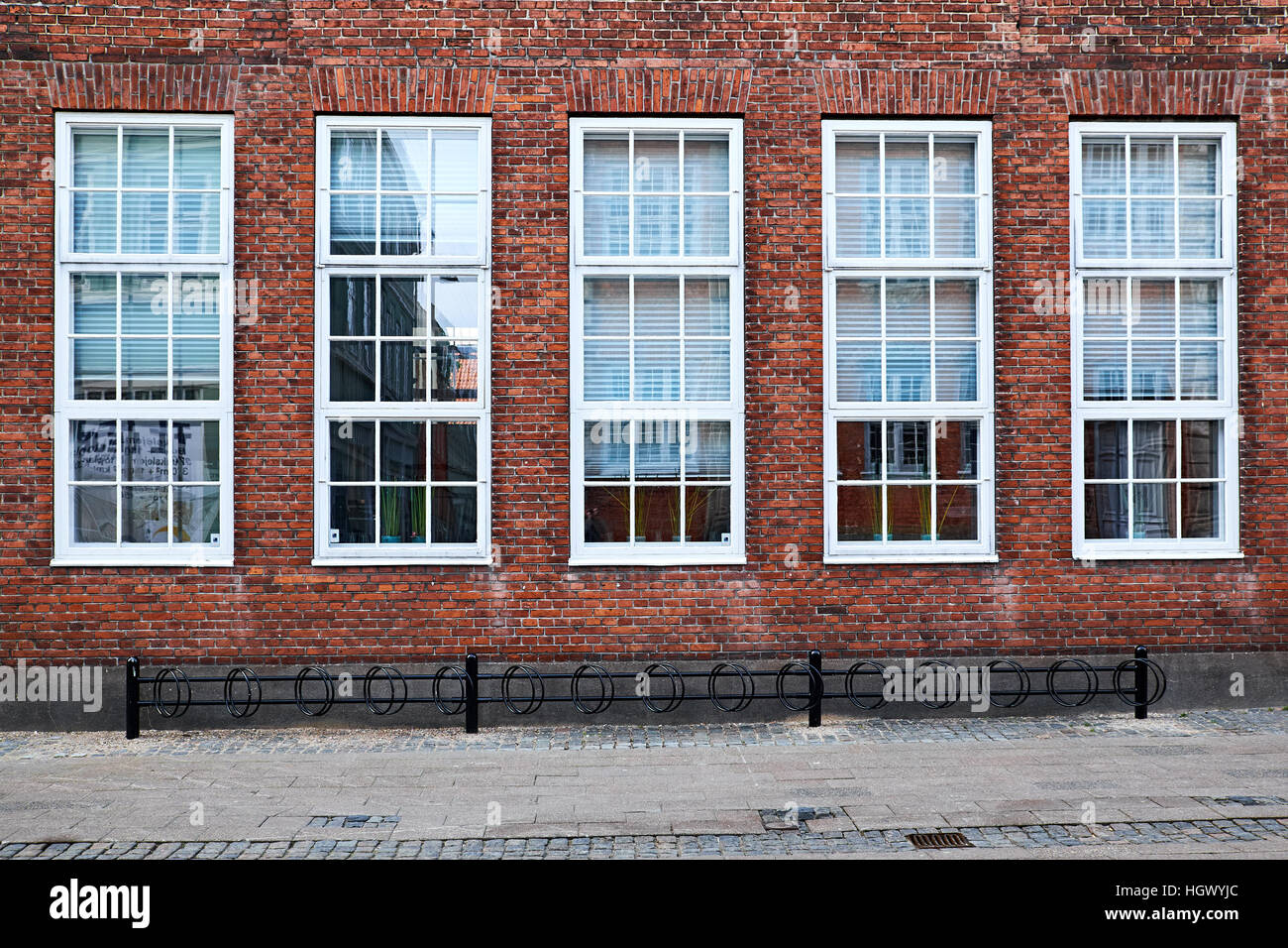 five tall white painted awning windows in a red brick facade facing the street, with a pavement and bicycle stands - Stock Image