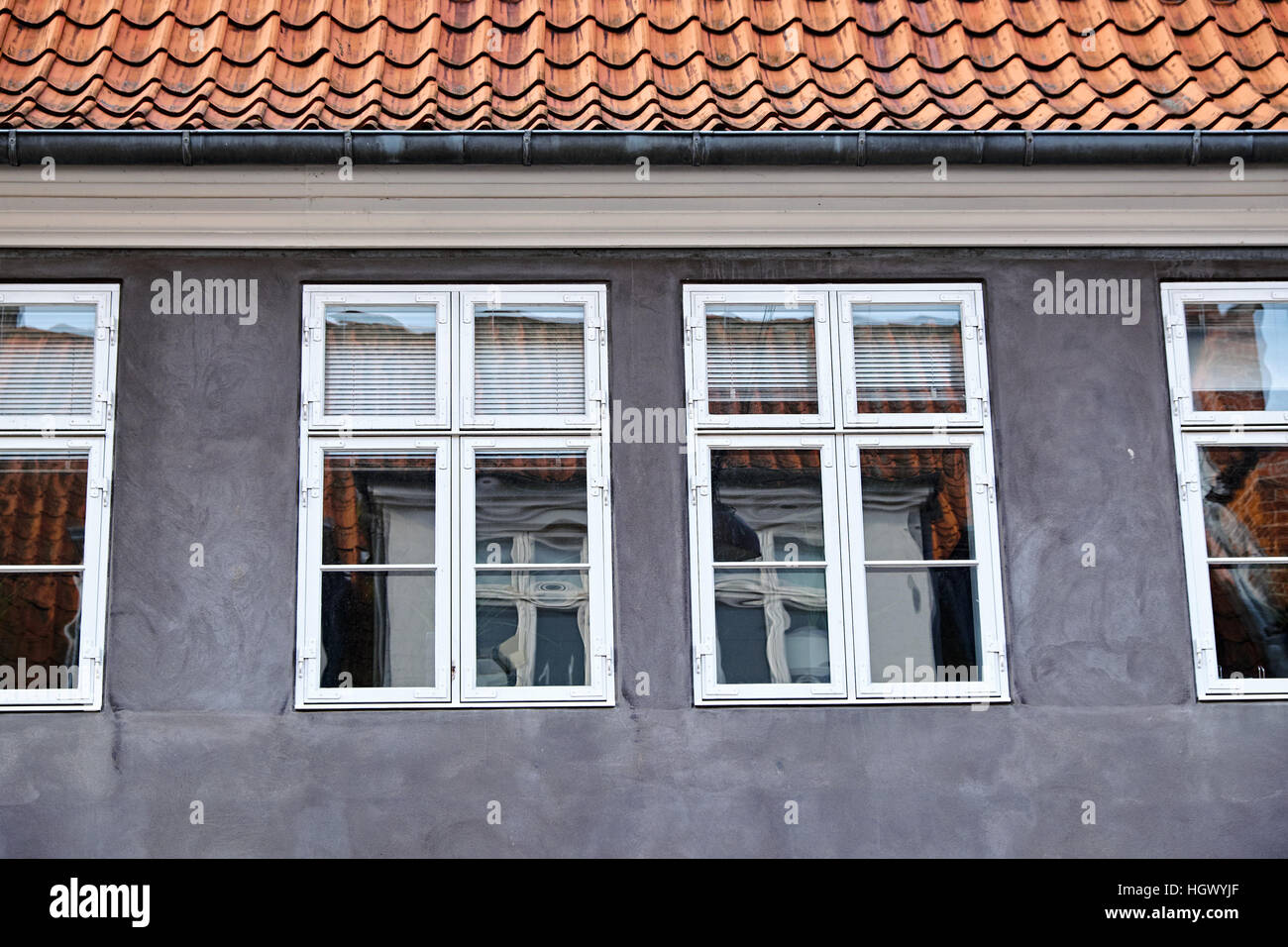 Gray plastered facade with white painted double casement windows, of wood, above is a roof with red clay tiles and - Stock Image