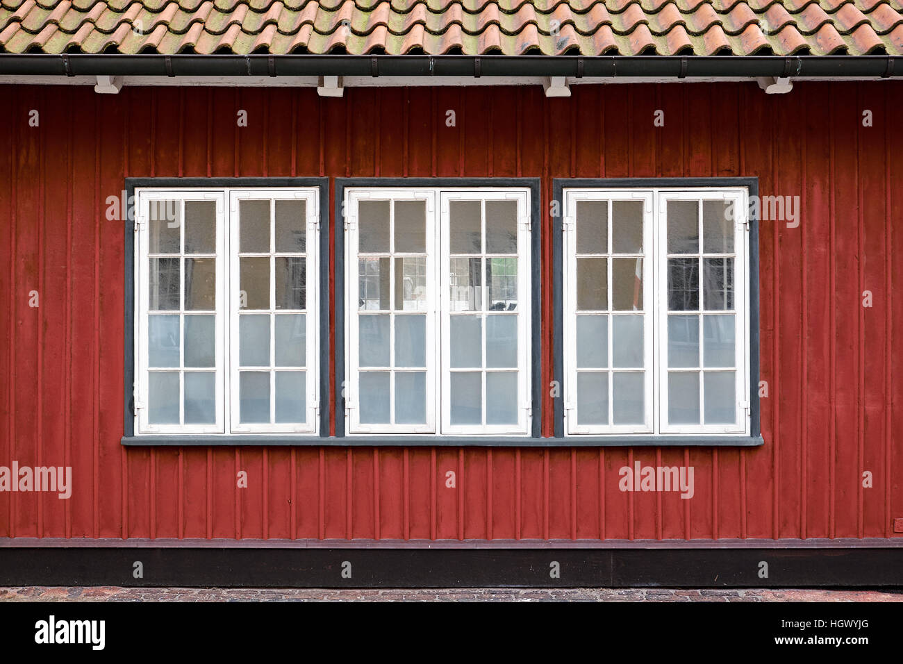 Three white painted casement windows with partly frosted glazing, in a red painted wood plank facade - Stock Image