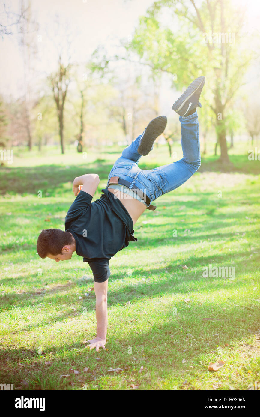Full body portrait of parkour man jumping high in the park Stock Photo