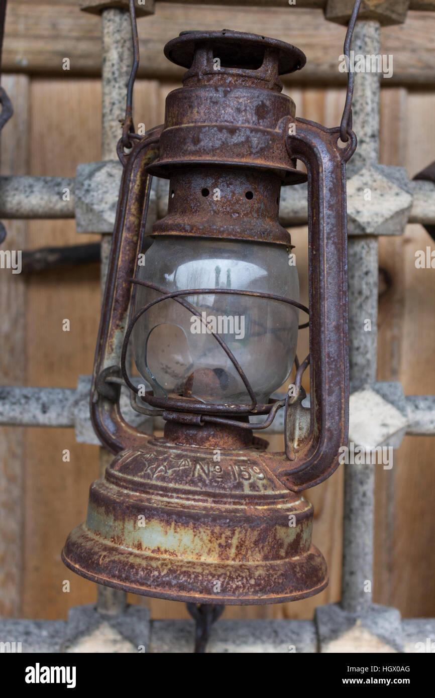 Old rusty kerosene lamp hanging on a metal grid in bulgarian village Zheravna - Stock Image