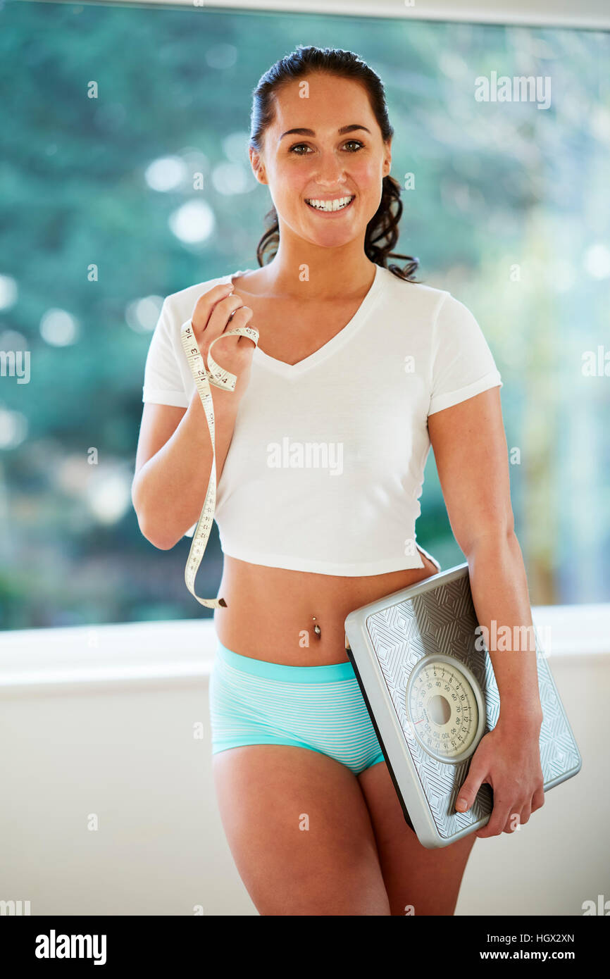 Beautiful girl holding scales and tape measure - Stock Image