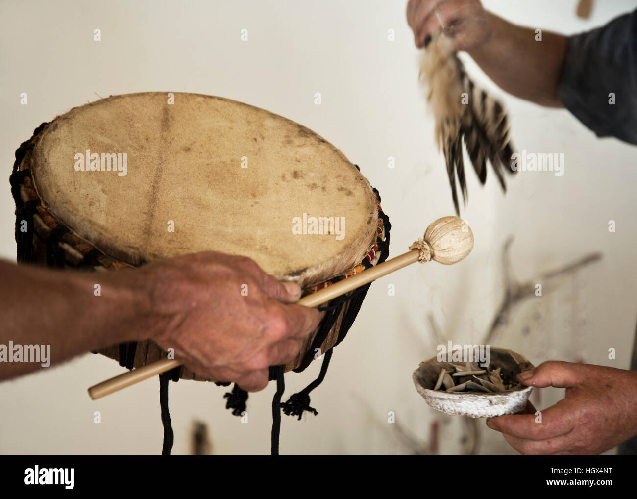 Shamanic smudge ceremony with sage, feathers and drum. Close up of hands holding the attributes. - Stock Image