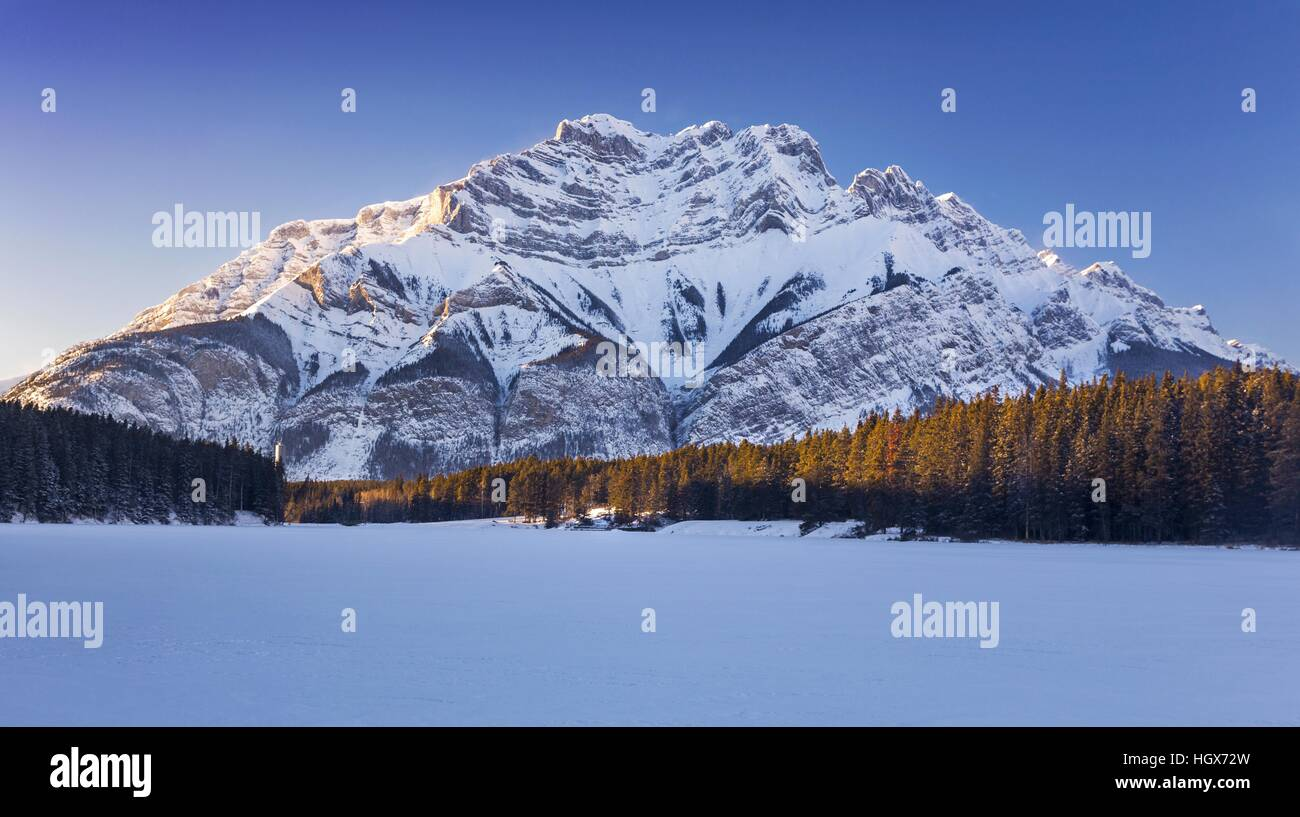 Frozen Johnson Lake and Distant Cascade Mountain Scenic Winter Landscape in Banff National Park Canadian Rocky Mountains - Stock Image