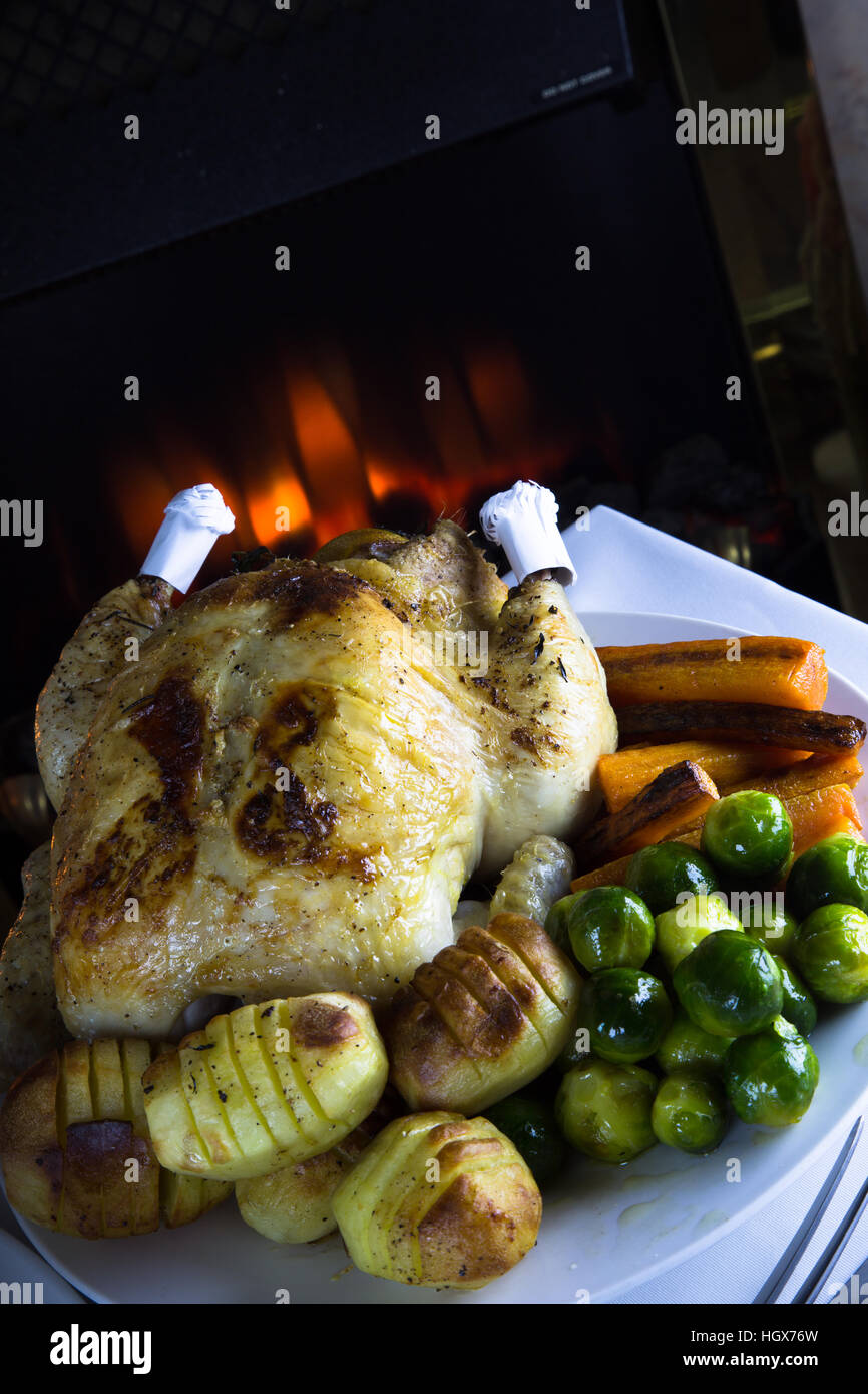 Whole Roast Chicken with potatoes and fresh cooked vegetables ready for serving. Stock Photo