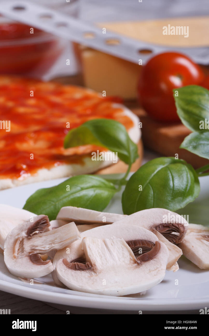preparation of ingredients for pizza: sliced mushrooms, basil, dough, tomato. Vertical - Stock Image