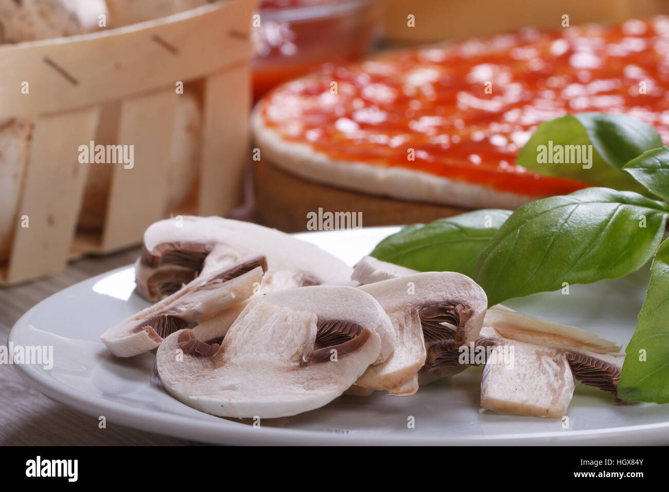 preparation of ingredients for pizza: sliced mushrooms, basil, dough, tomato. horizontal - Stock Image