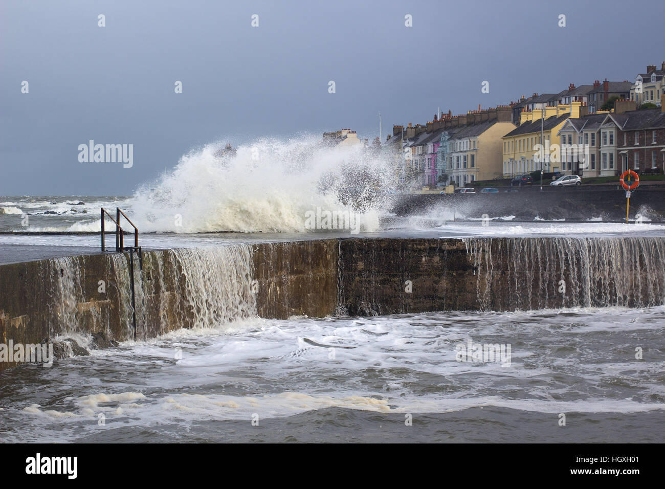 A winter storm buffets a harbor wall sending waves foam and spray into the air and curtains of water cascading into - Stock Image