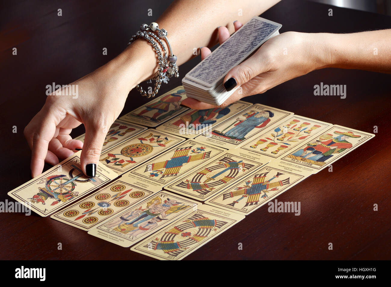 Female fortune tellers hands spreading vintage tarot cards on dark table surface - Stock Image