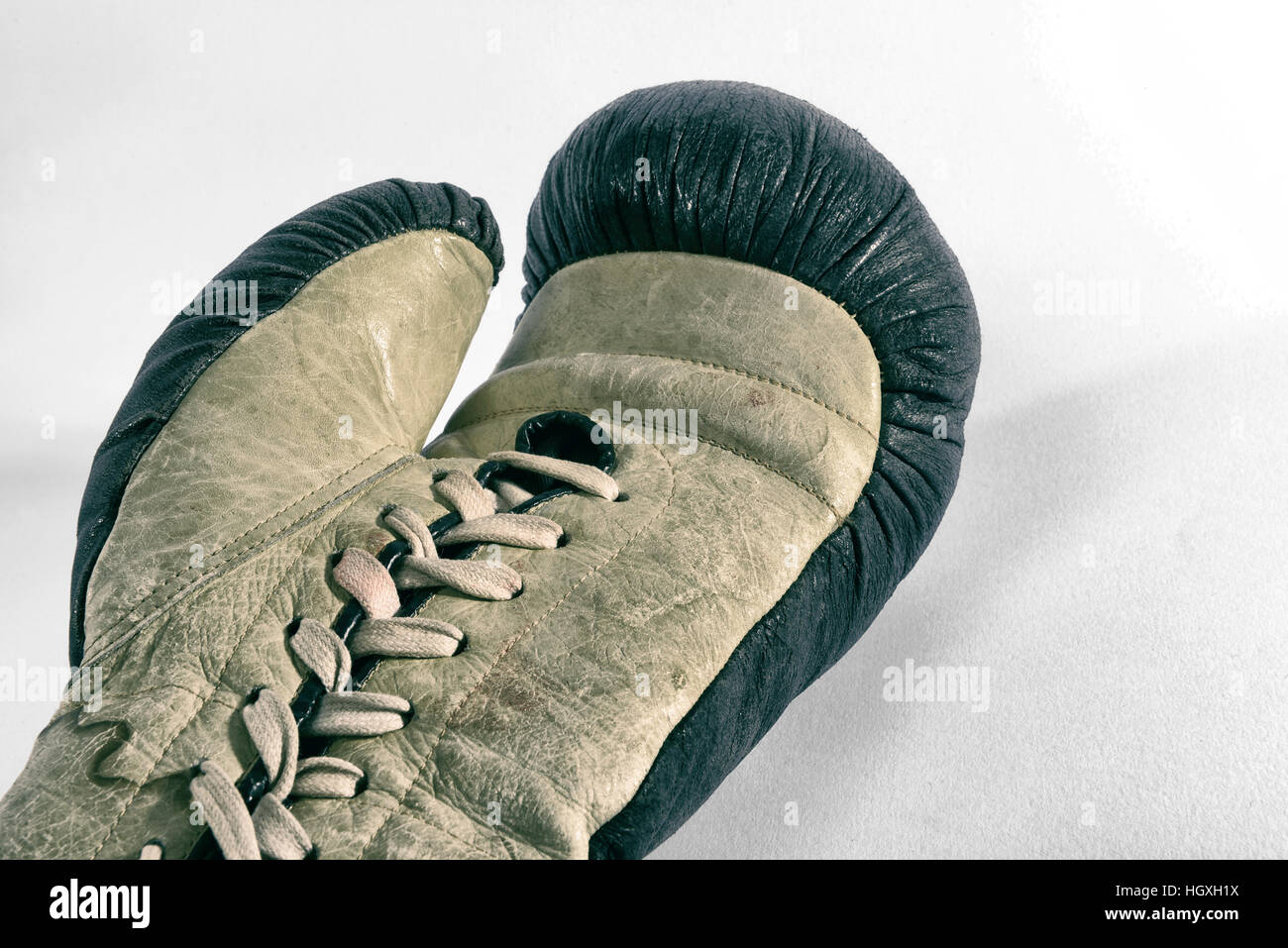 Crop view of single vintage boxing leather glove with laces laying on white surface - Stock Image