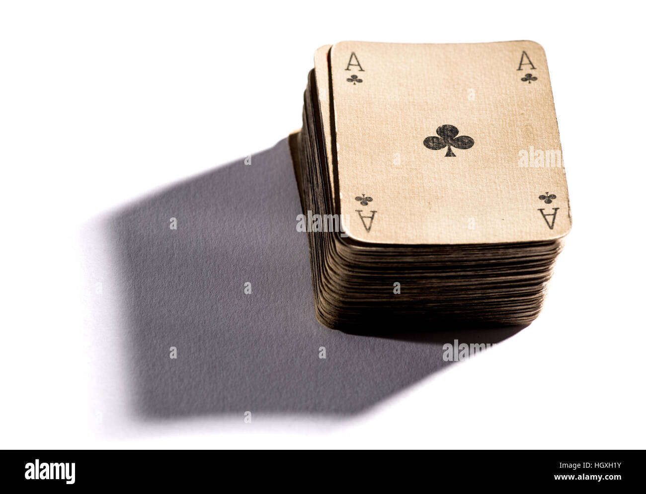 Deck of vintage old playing cards of faded withered paper with the ace of clubs on the top, dropping shadow on white - Stock Image