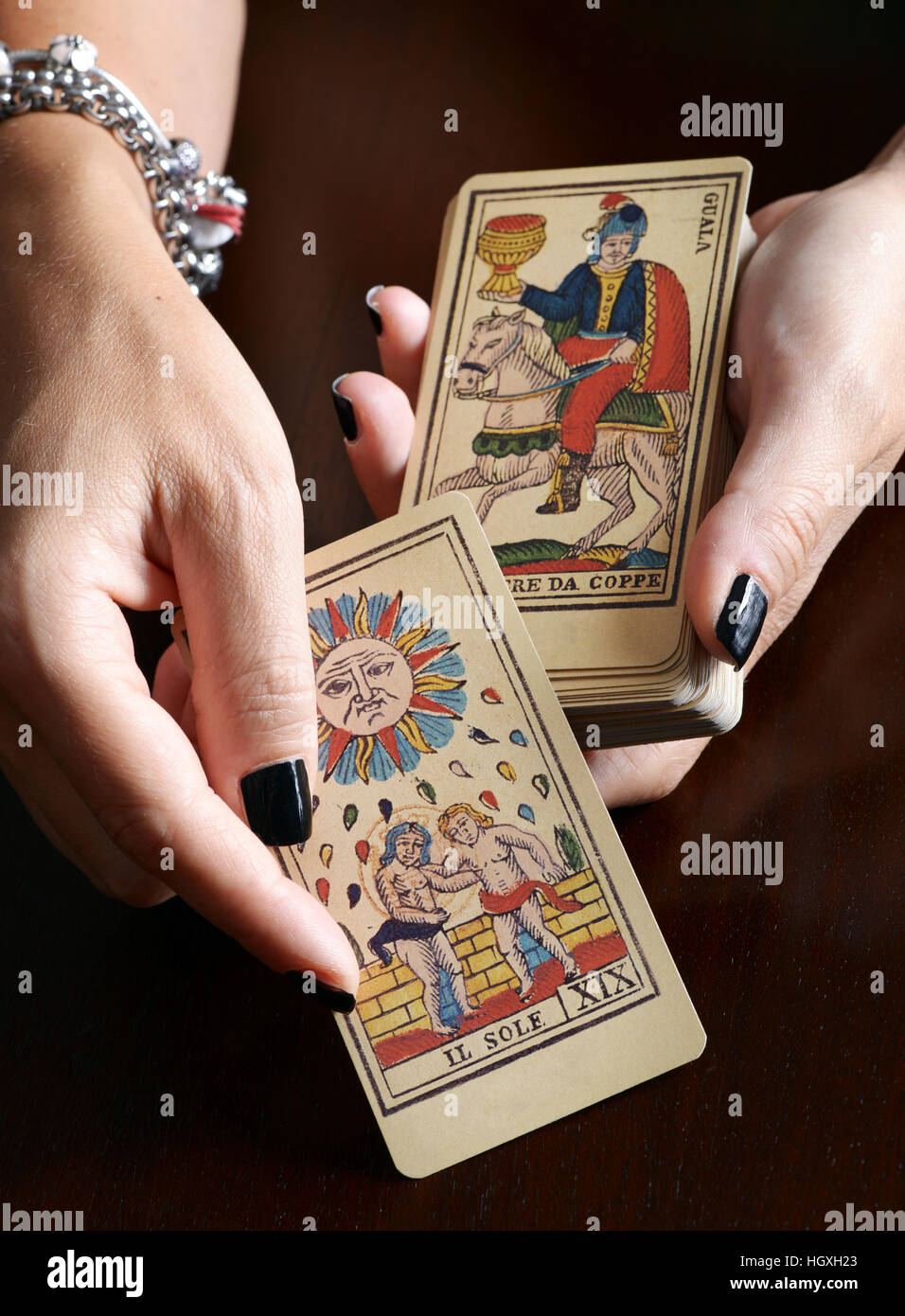 Close up view female hands with black nail art and bracelet showing old tarot card and card deck over dark table - Stock Image