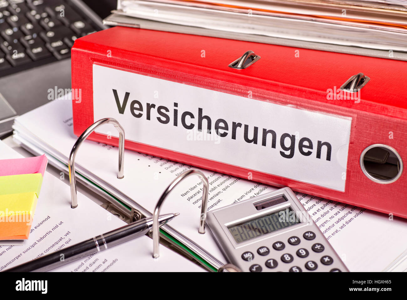 Red file folder with the label 'Versicherungen' for insurance. - Stock Image