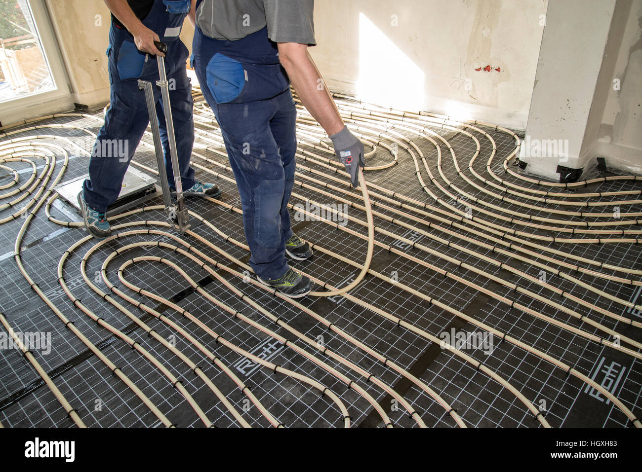 Craftsmen when laying pipes of underfloor heating - Stock Image