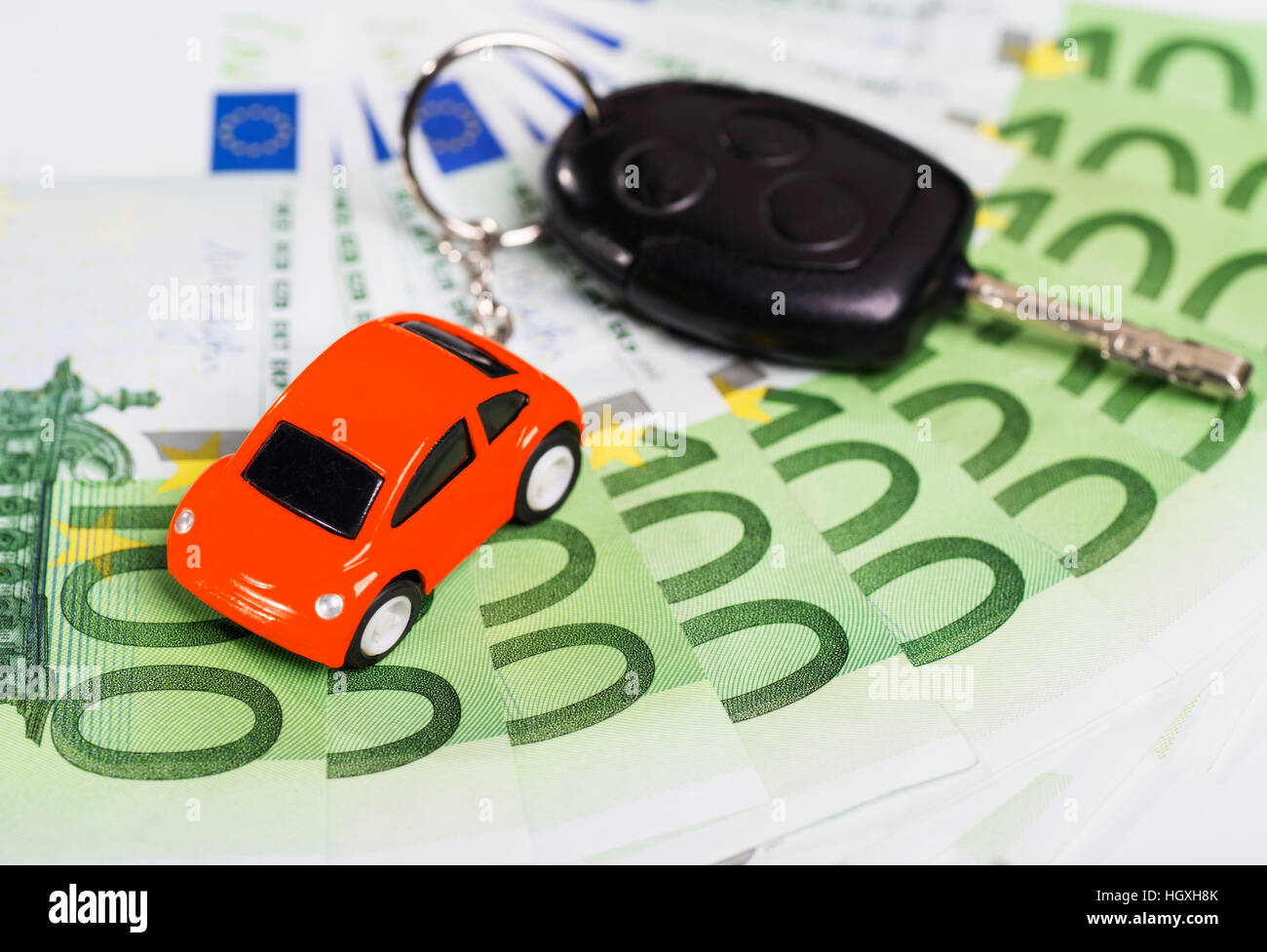 Car key with banknotes and key hanger in the form of a car - Stock Image