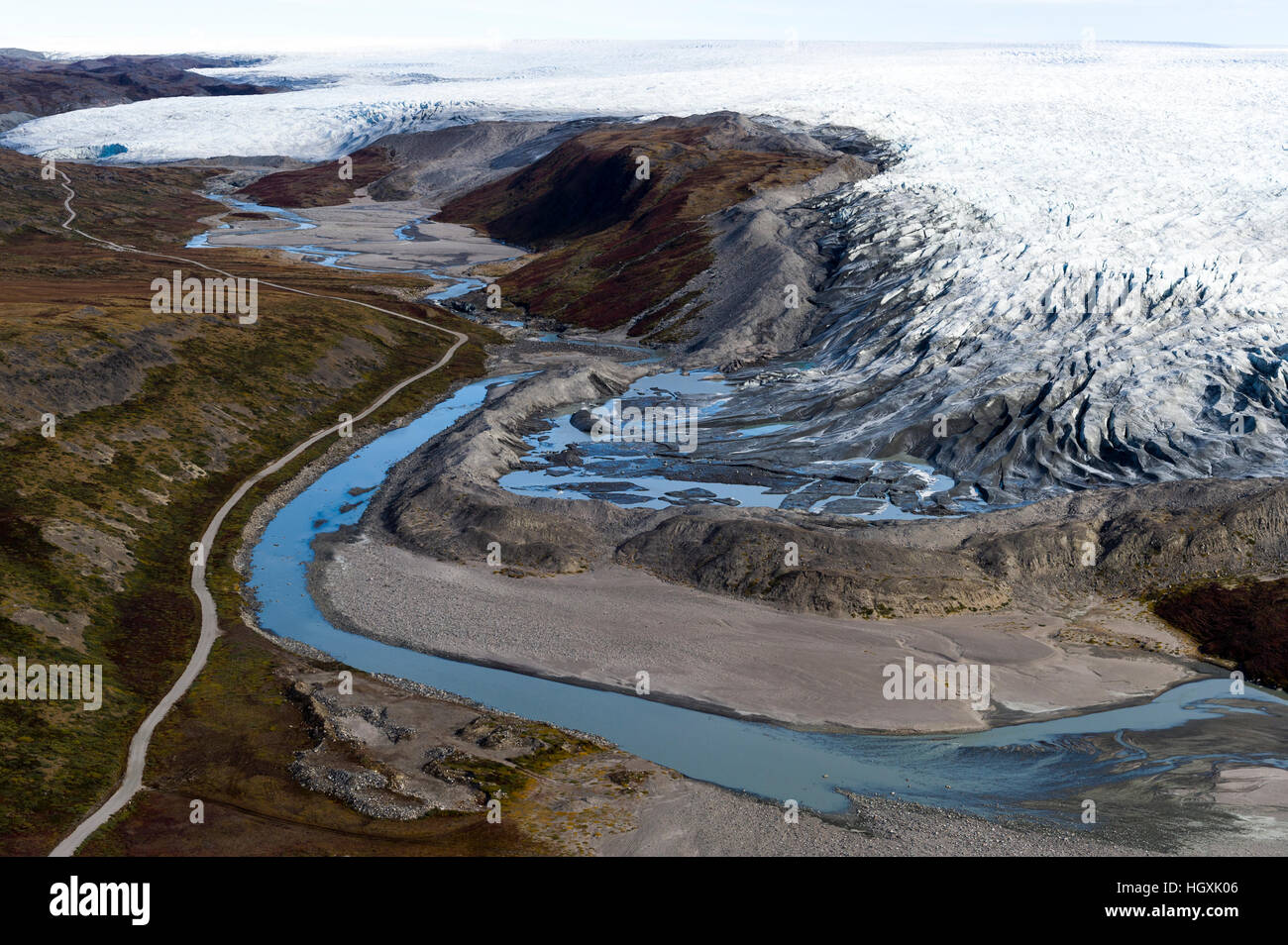 A river skirts a pile of rock, sediment and silt debris deposited by the leading edge of a glacier. - Stock Image