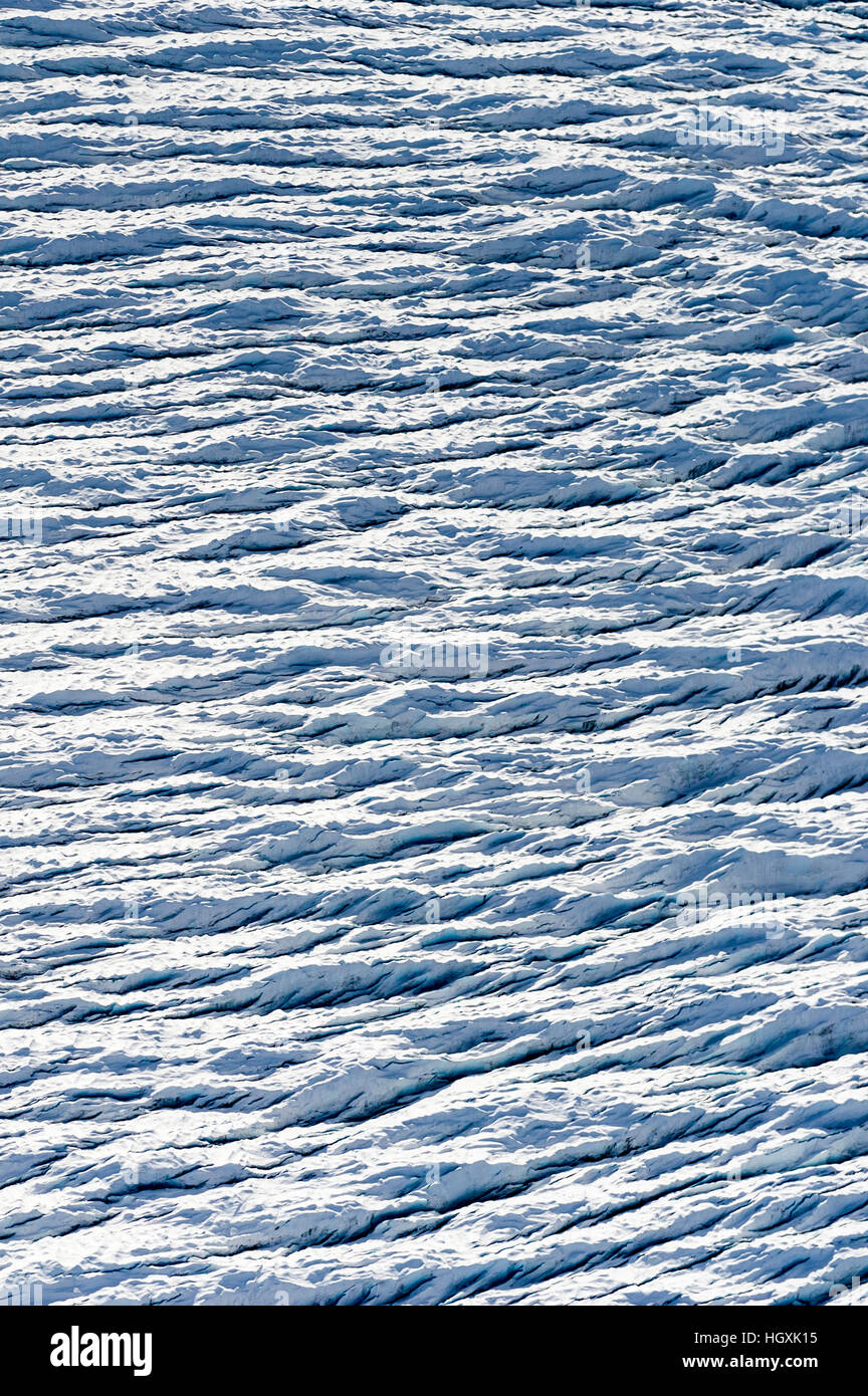 Pressure ridges and crevasse scar the surface of a glacier on the Greenland Ice Sheet. - Stock Image