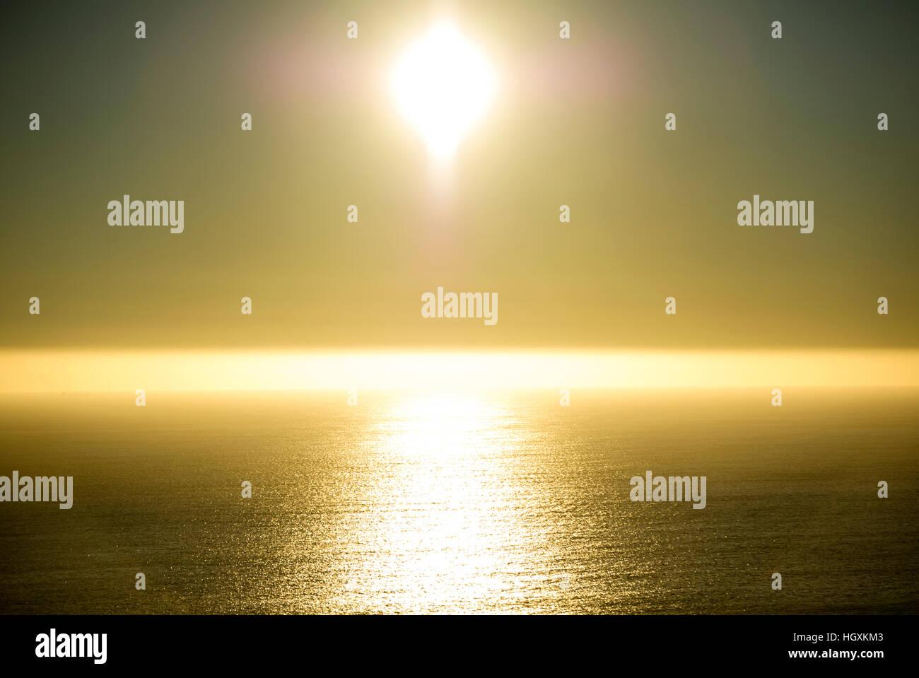 The sun casts a golden pillar on the ocean as it dips toward sunset. - Stock Image
