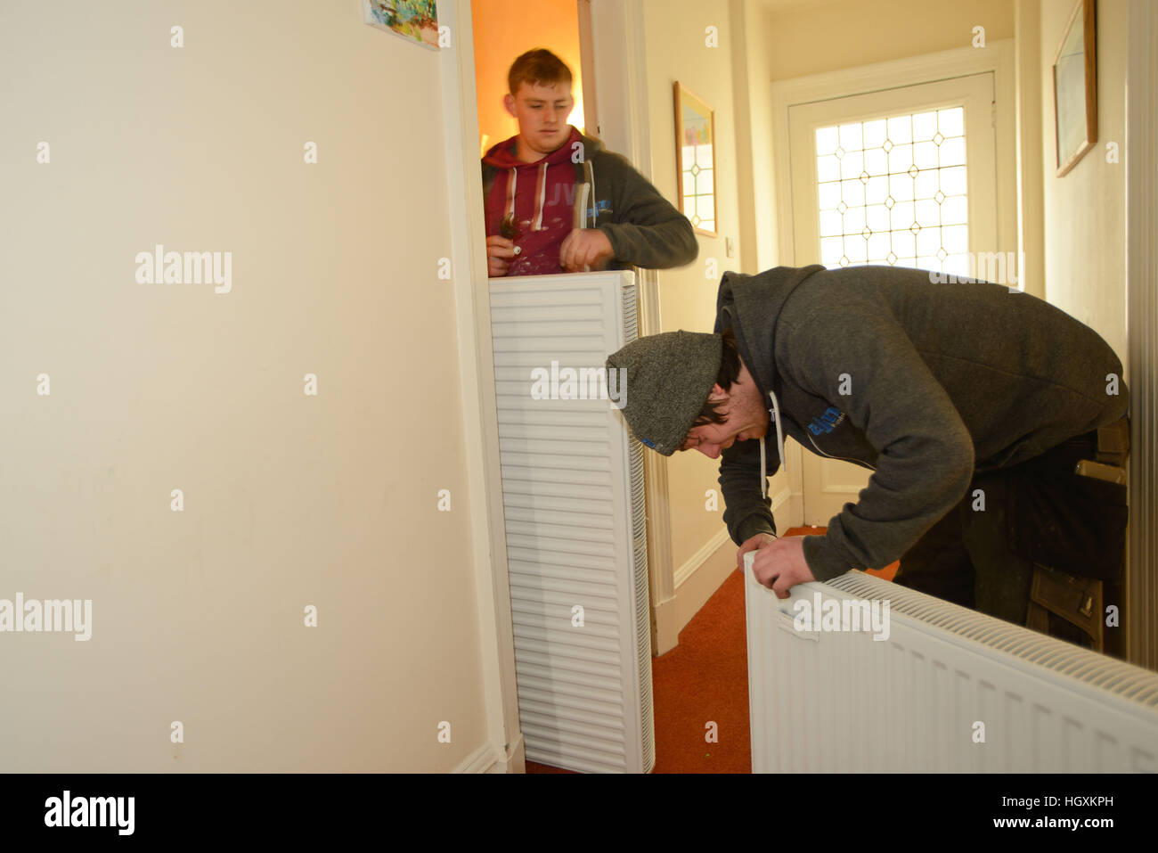 Plumbers fitting new radiators in an old house in Aberdeen Scotland - Stock Image