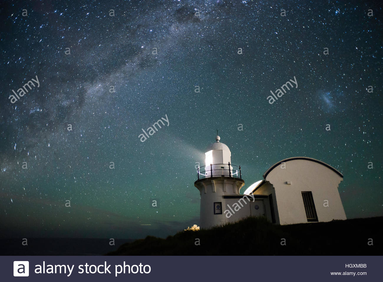 Port Macquarie lighthouse shines in the foreground with the Milky Way lighting up the night sky behind. - Stock Image