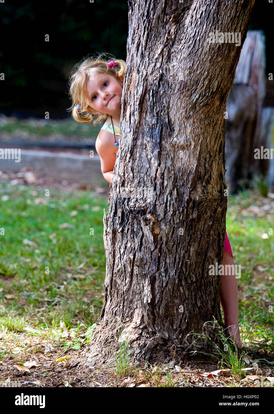 Little girl plays hide and seek - Stock Image