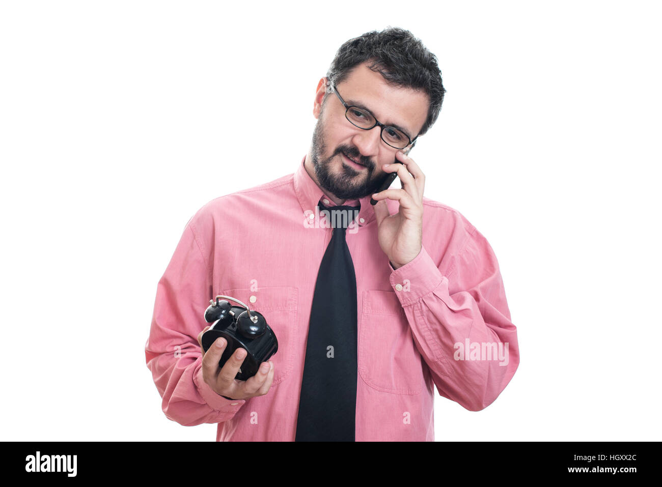 Smiling man with alarm clock talking at his smart phone Stock Photo