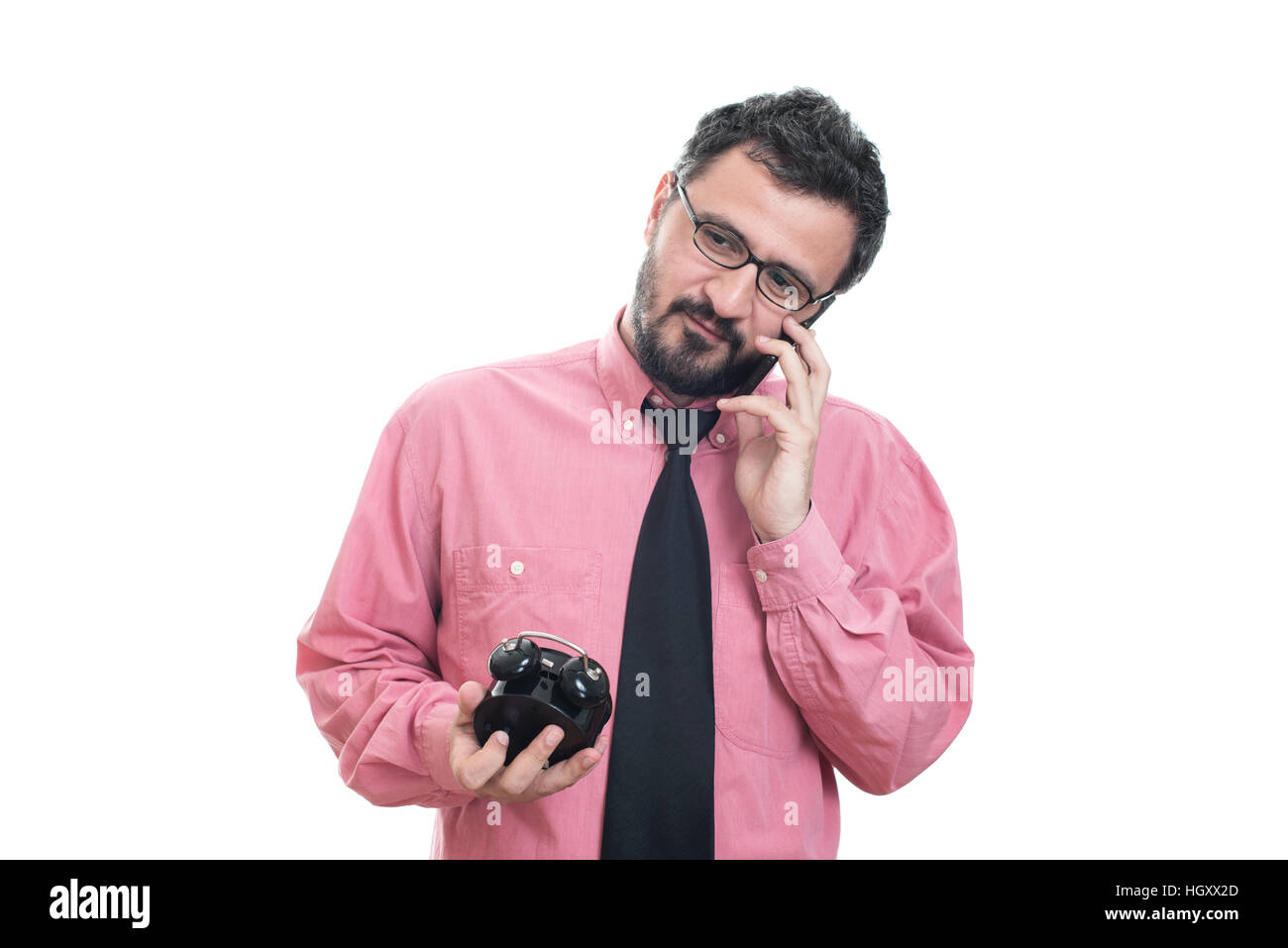 Smiling man with alarm clock talking on smart phone Stock Photo