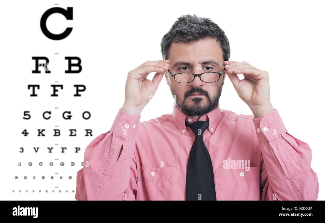 Man taking an eye exam and wearing glasses Stock Photo