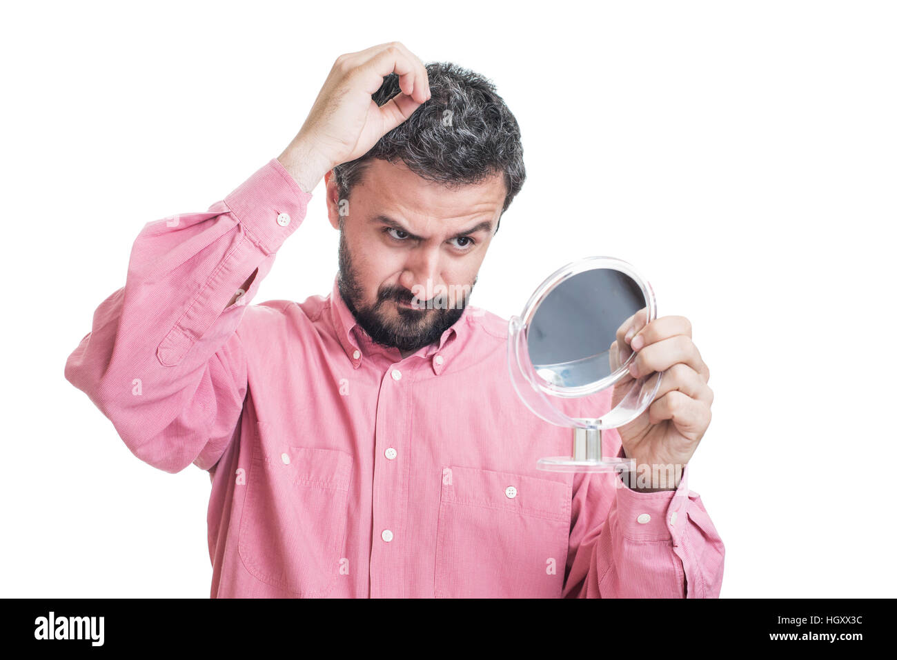 Man worried about gray hair looking in a mirror Stock Photo