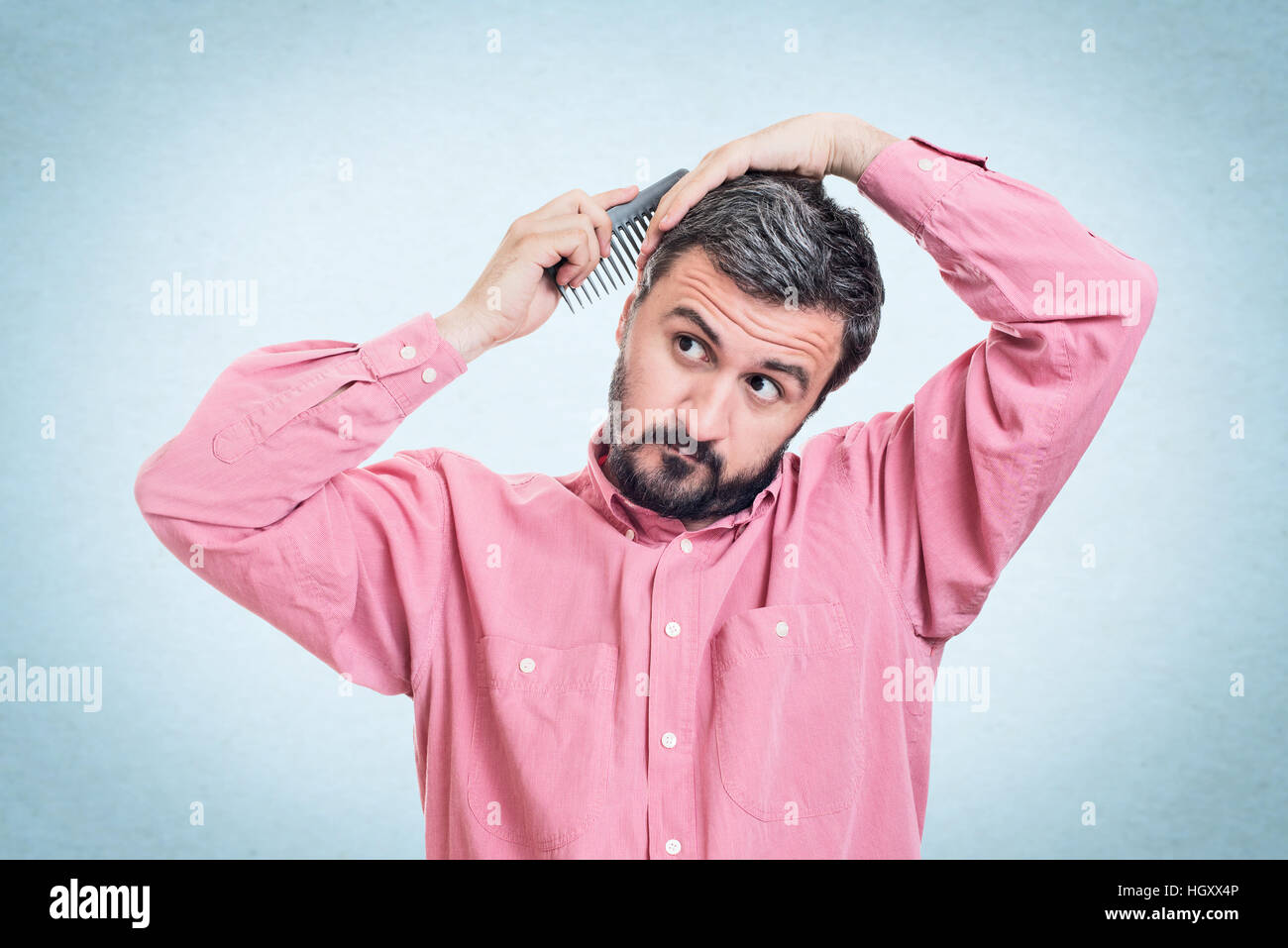 Handsome young beard man combing his hair Stock Photo
