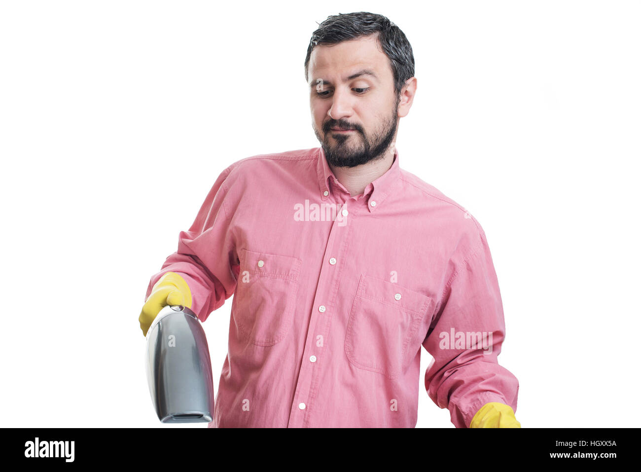 Smiling young man with handheld vacuum cleaner Stock Photo