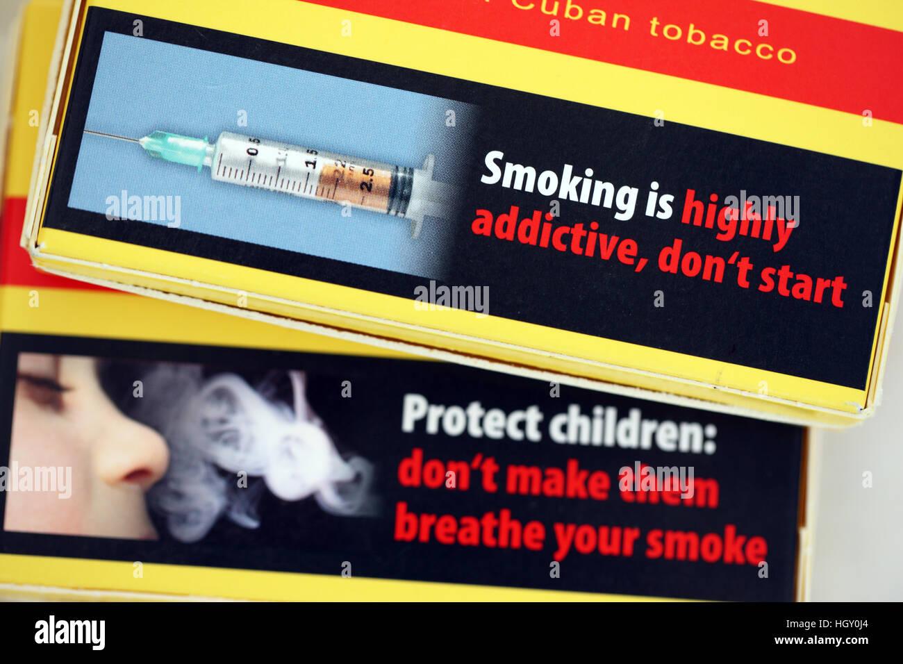 Smoking health warnings on cigar packets - Stock Image