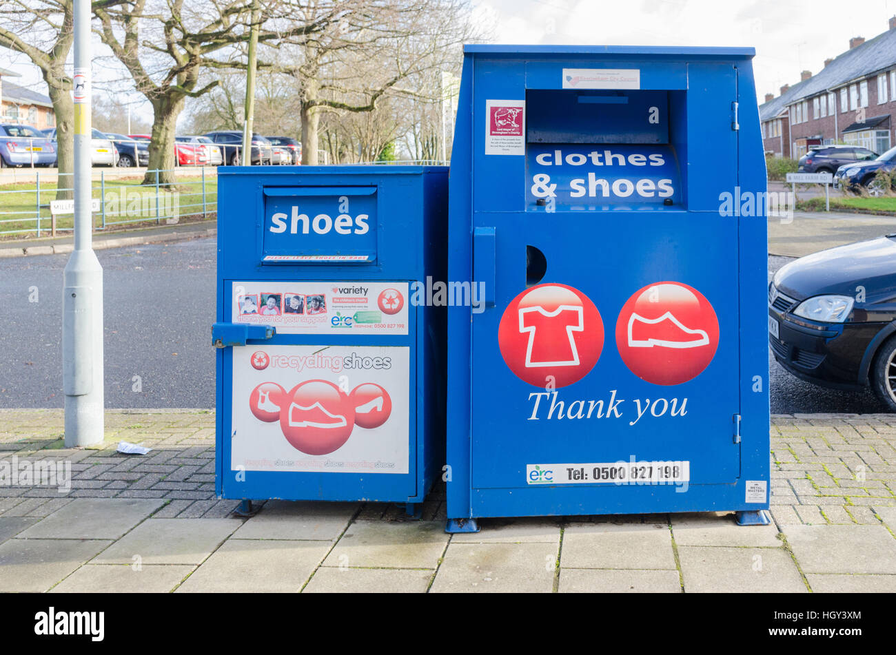 Blue collection bins for clothes and shoes on the pavement - Stock Image