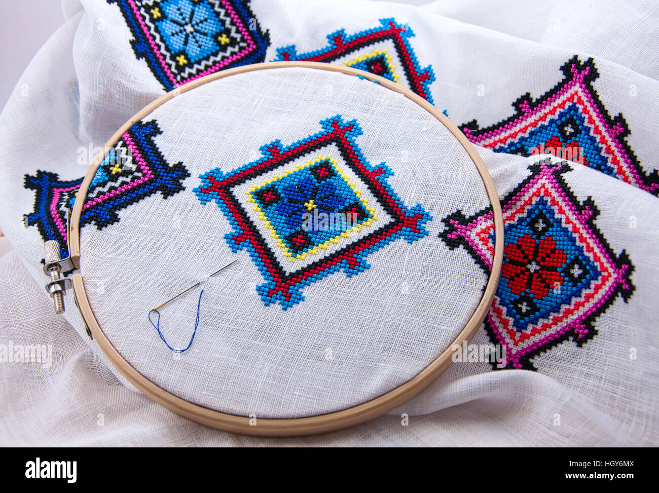 Traditional Slavic geometric pattern embroidered cross stitch multicolored thread, white fabric in the wooden embroidery - Stock Image