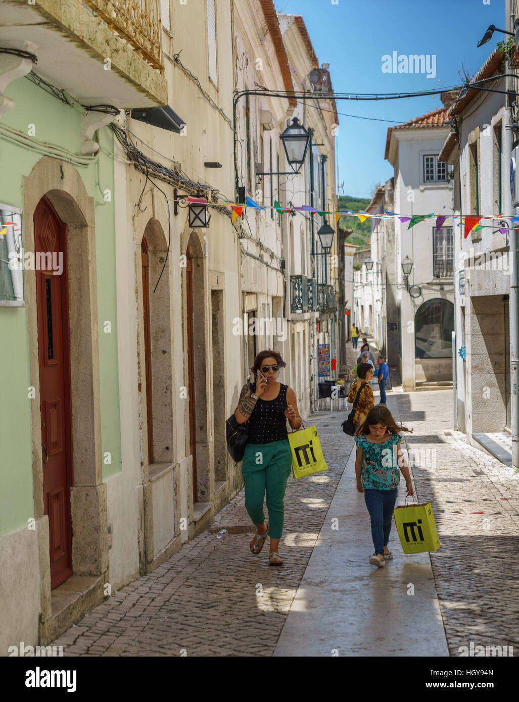 Shoppers carrying bags in the narrow cobblestone streets of Torres Vedras Portugal - Stock Image