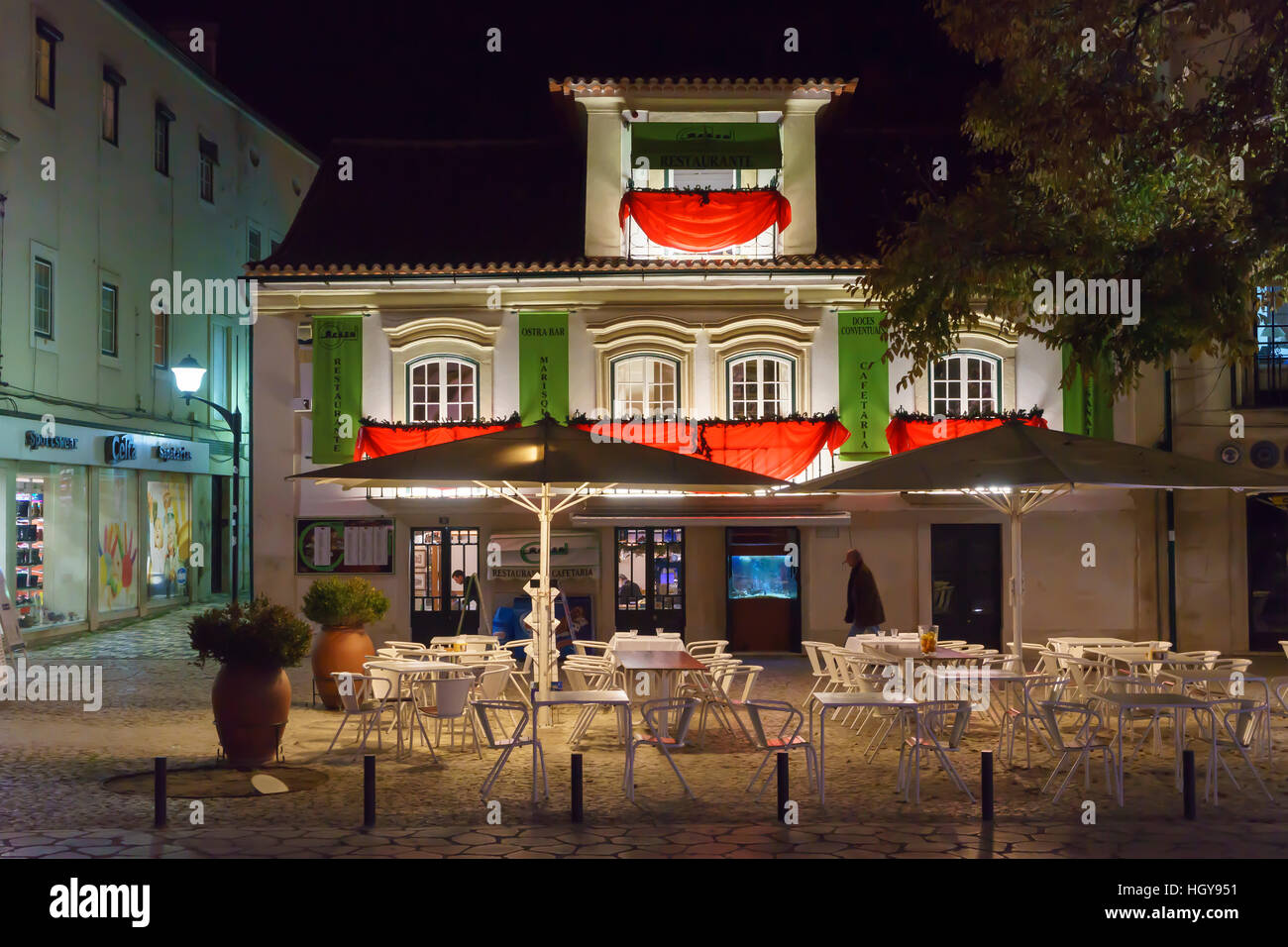 Brightly lit cafe with outside seating by night in Alcobabca, Portugal - Stock Image
