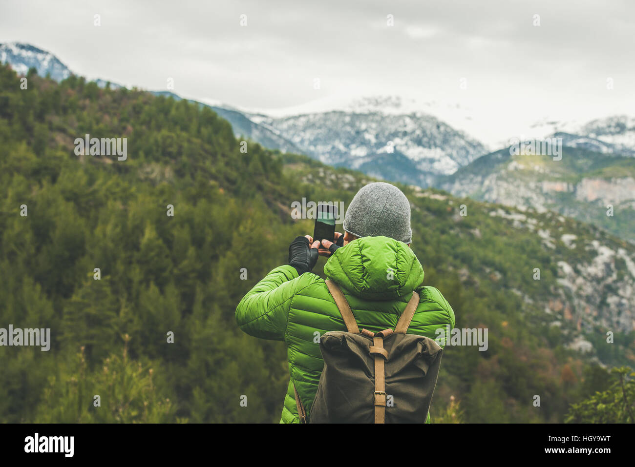 Young man traveller making photo of mountains and green slopes - Stock Image