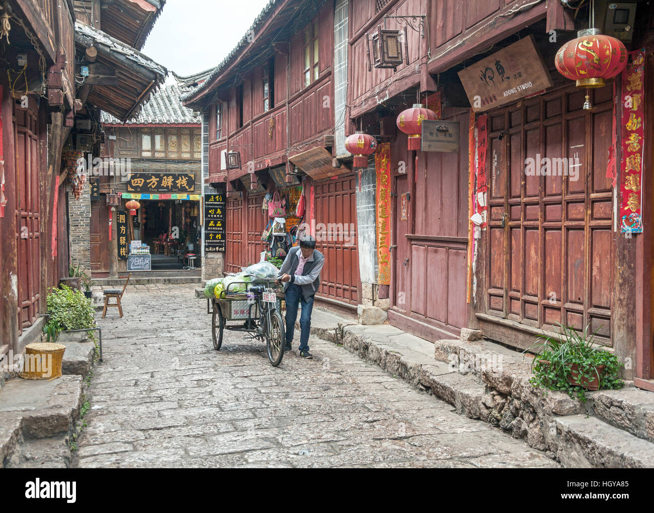 LIJIANG, CHINA - SEPTEMBER 17, 2014: vegetables trader transports its products to the market in the tourist center - Stock Image